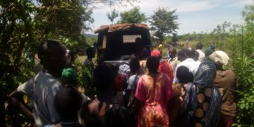 Villagers view the body of the man in a police vehicle before it was taken away