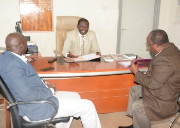 Trans Nzoia County Commissioner Samson Ojwang (centre) in his office. Photo/Courtesy