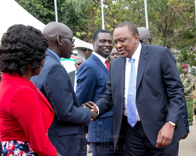 President Uhuru Kenyatta greets Education PS Belio Kipsang at KICC during the National Conference on curriculum reforms. Photo/PSCU