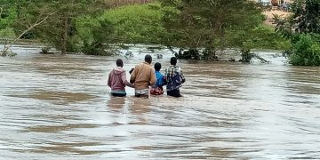Locals try to cross flooded river Malakisi at Machakus bridge in Busia County some weeks ago