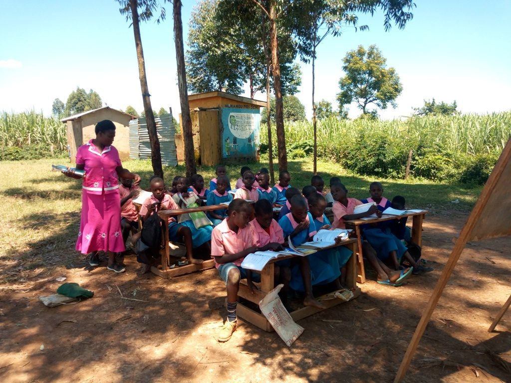 Some of the pupils taking classes under trees