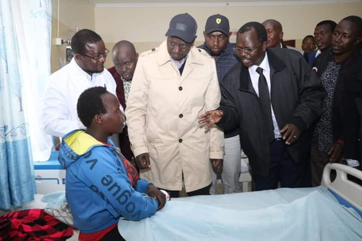 Deputy President William Ruto and West Pokot Governor John Lonyangapuo interacting with one of the victims