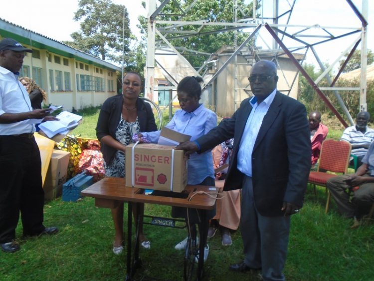 The NFDK CEO Alex Mutegi (right) with the Lugari ACC I Nancy Kiptoo (left) giving a sewing machine to a disabled person