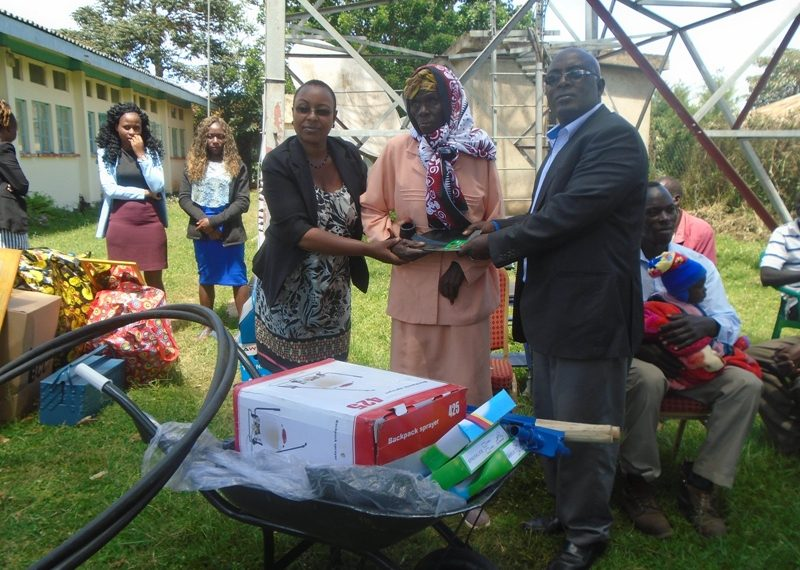 The NFDK CEO Alex Mutegi (right) with the Lugari ACC I Nancy Kiptoo (left) giving farm implements to a disabled person
