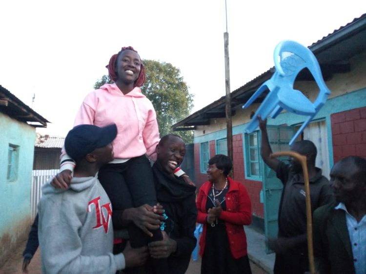 Long'ali Chepengat being hoisted by residents after her great KCSE performance