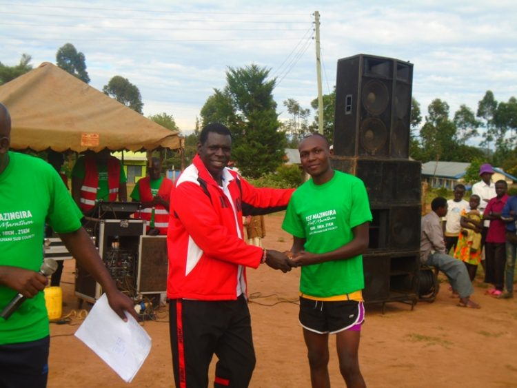 Kakamega County Sports CEC Robert Makhanu with the 21km champion Brian Wekesa