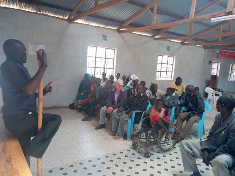 Moses Nanjukhi (left) addressing persons living with disabilities