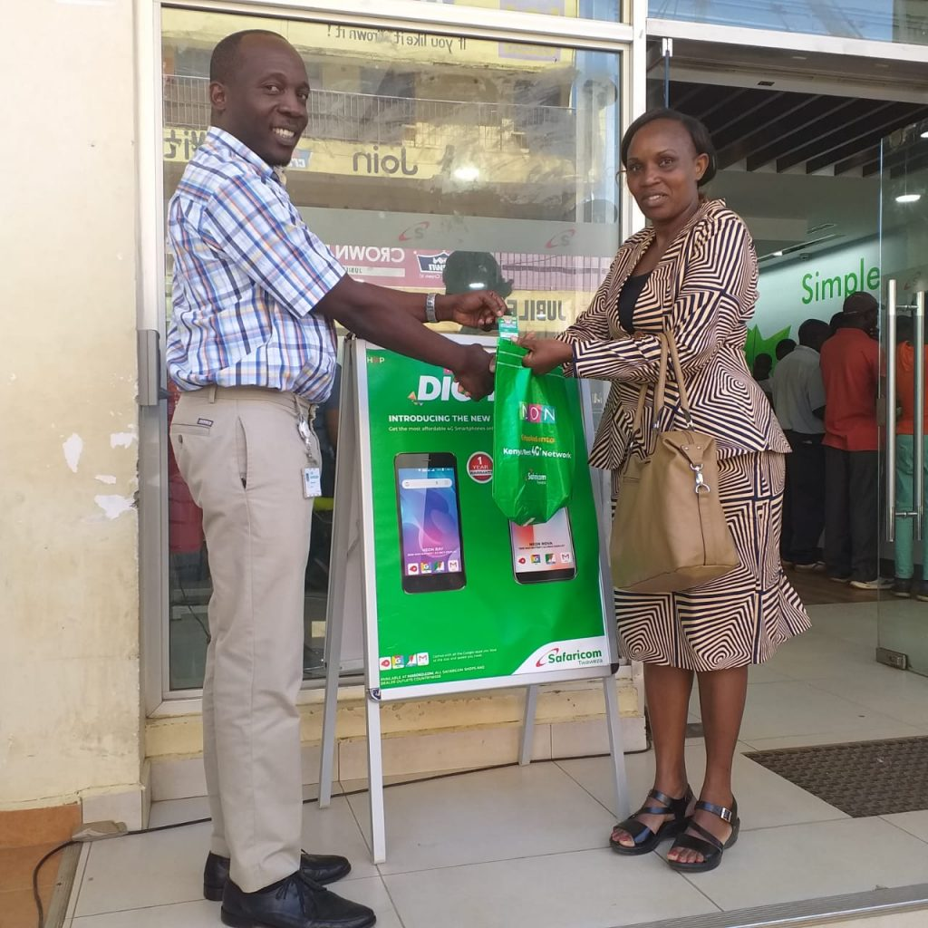 Safaricom Kakamega Branch Manager Stephen Okich handing airtime Prize to a lucky customer