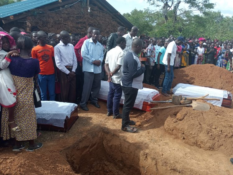 Caskets of three family members at the dug graves