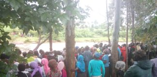 A crowd of onlookers at the bank of river Kipkaren where the body was found
