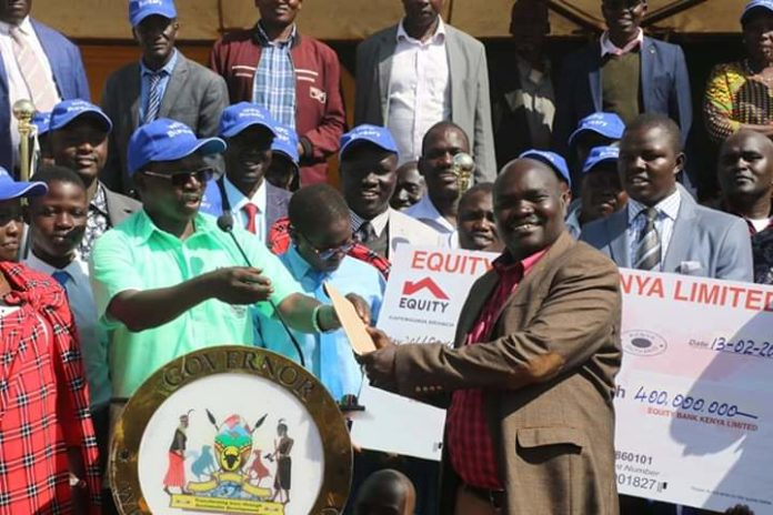 West Pokot Governor John Lonyangapuo (left) launching the bursary kitty