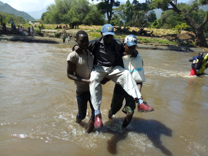 Youths carrying a man while crossing Chepar river, whose bridge was submerged in water