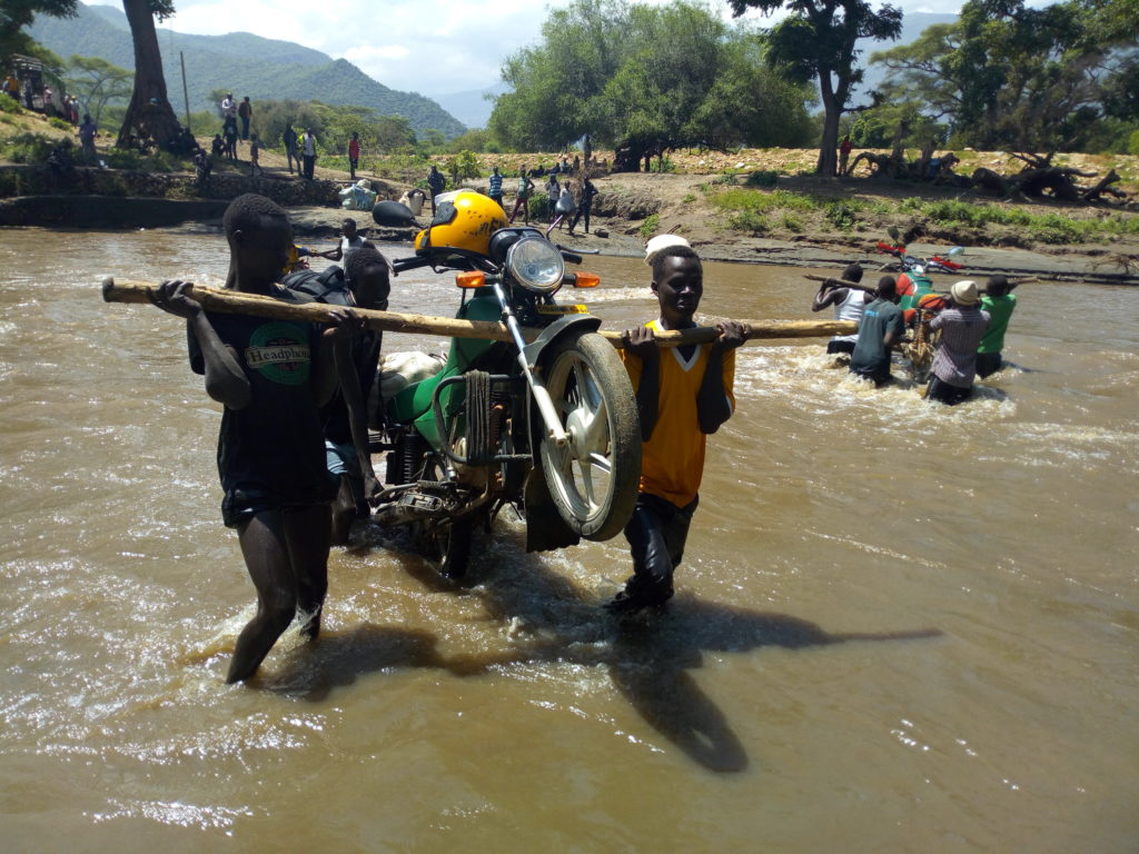 Youths carry a motorbike while crossing Chepar river