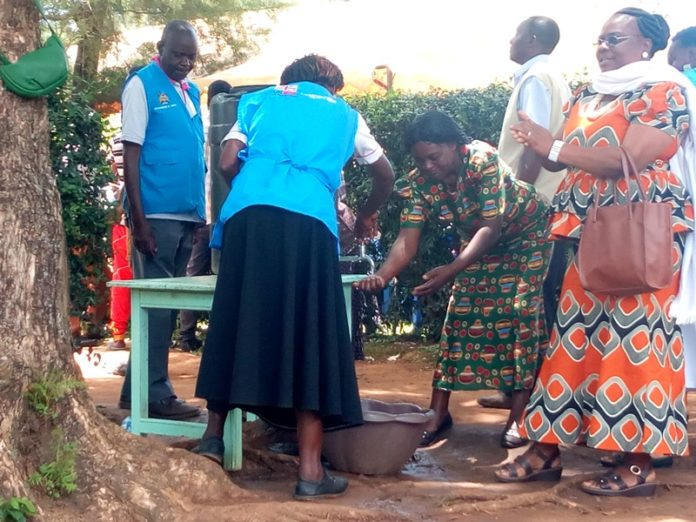 Mourners washing their hands at the gate before they could be allowed to the burial service