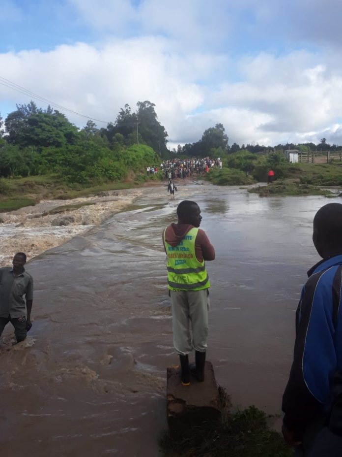 Residents and business people stranded along Mayanja stream after heavy floods covered the bridge that connects Lunao and Myanga markets
