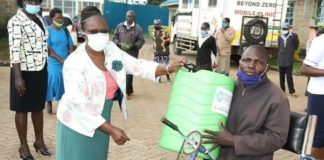 Nandi Deputy Governor Dr Yulita Cheruiyot handing out a hand washing container to a resident in Emgwen