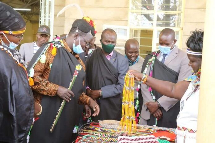 West Pokot Governor John Lonyangapuo(left) among other leaders observing bead products