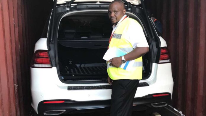 A Kenya Revenue Authority (KRA) official inspecting an impounded luxurious car