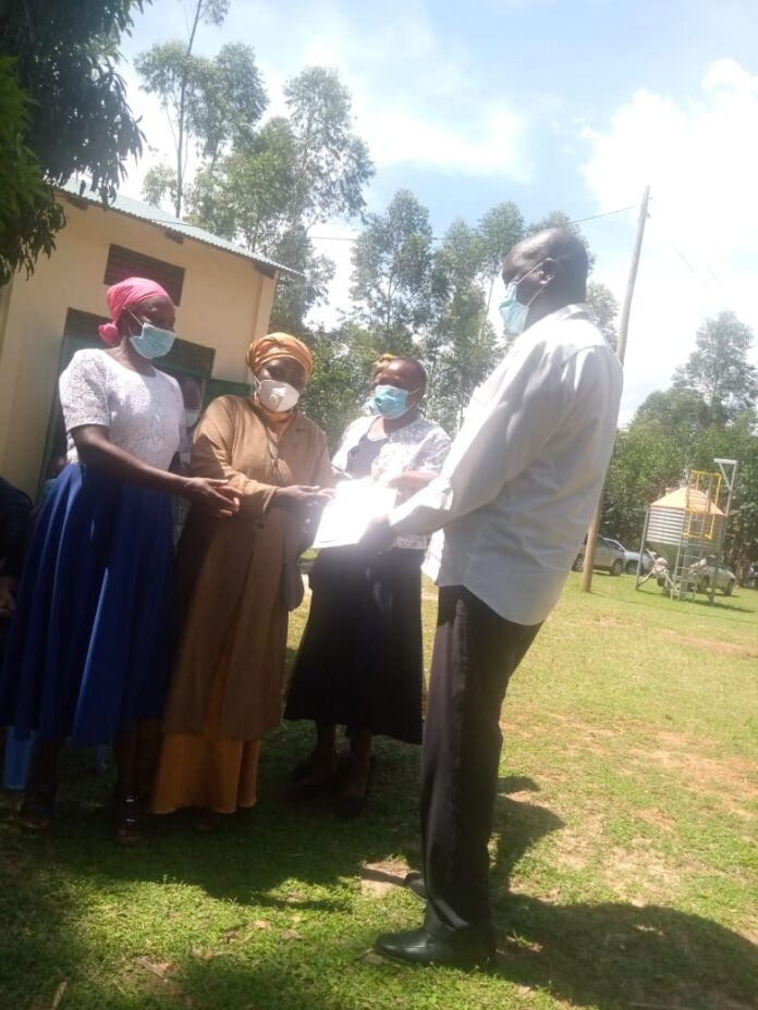 Isaac Sang Kosgei handing over cash to the group