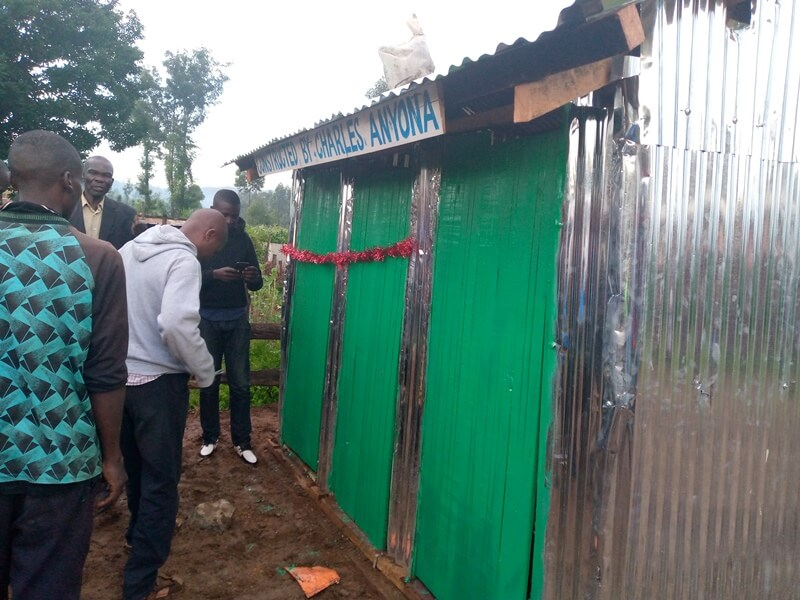 Mr. Charles Anyona in a grey jumper when he commissioned the toilets